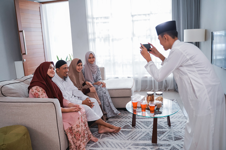 Hombre musulmán tomando una fotografía de su familia mientras está sentado en un sofá