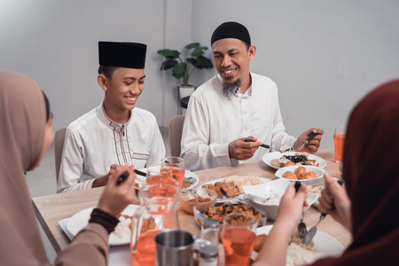 muslim father and son eating some dinner together