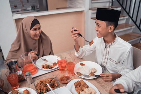 muslim mother talking to her son while having dinner together