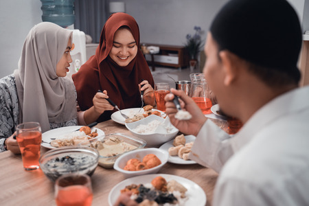 muslim asian family enjoy the iftar meal together in dining room 版權商用圖片