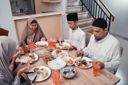 muslim family together pray before meals