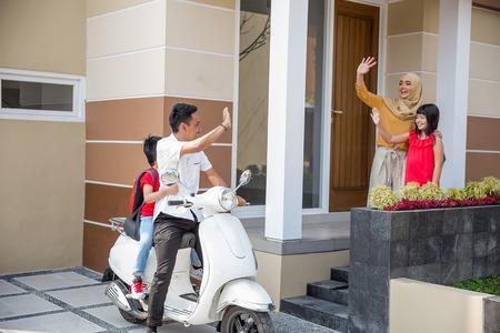 ojciec i syn jadą na skuterze do szkoły