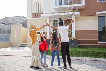 dos niños con sus padres divirtiéndose juntos frente a su nueva casa Foto de archivo