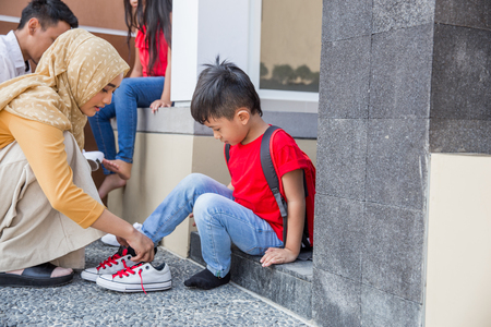 happy asian mother with hijab help his son to put on his shoes Standard-Bild - 123332687