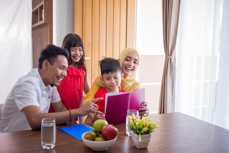 Aziatische familie die thuis samen een boek leest