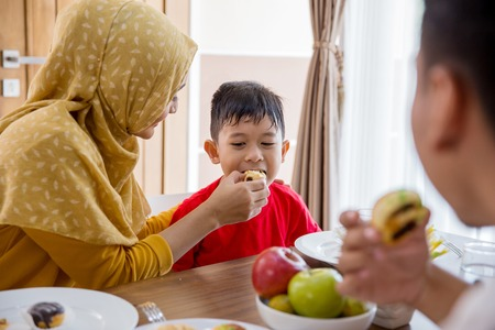 muslim mother feeding her little boy at home