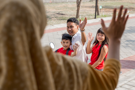 portrait of daddy taking his kids to school by motor bike waving goodbye to mommy