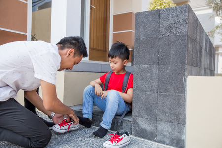 help his son to put on his shoes Standard-Bild - 123430469