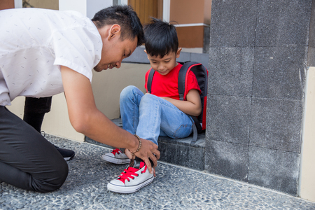 help his son to put on his shoes Stock Photo