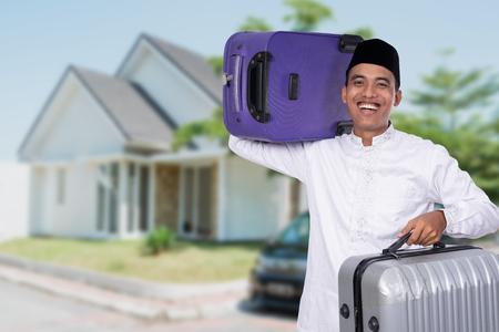 muslim male carrying suitcase for eid mubarak celebration