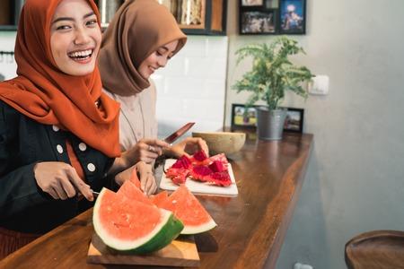 portrait hijab young woman slice watermelon