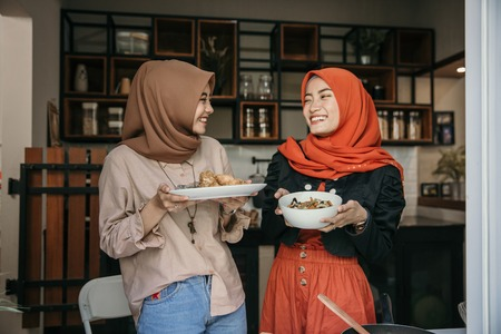 woman hijab carrying cuisine to serve when breaking fast