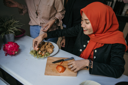 Asian woman hijab plating a cuisine with tomato
