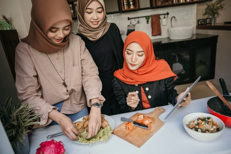 hijab woman and friends plating a cuisine in the kitchen Stock Photo