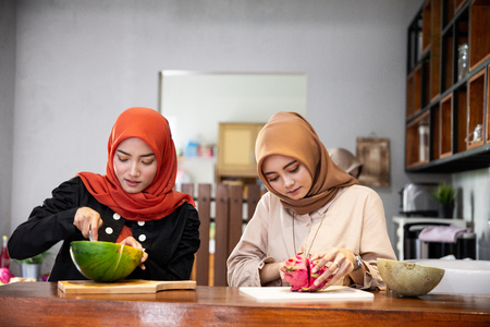 Two asian woman hijab prepare some fruits to make cocktail