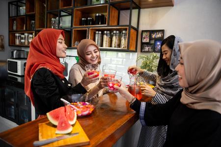 hijab women enjoy sweet drink when breaking fast together Stok Fotoğraf