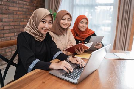看照相机的年轻美丽的妇女被遮掩的微笑着坐与膝上型计算机,片剂和书时