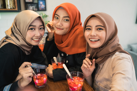 Veiled young women look at camera relaxing using smartphone for selfie
