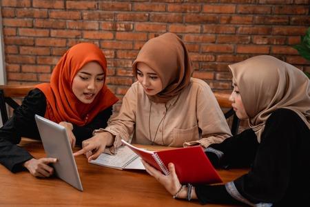Gruppe von College-Studenten, Freunden mit digitalem Tablet und Büchern Standard-Bild