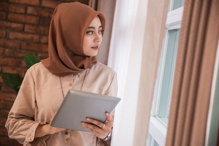 young beautiful woman veiled holding tablet and look out of windows standing near curtains