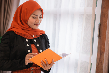 young woman hijab holding and looks a book standing near windows Stok Fotoğraf