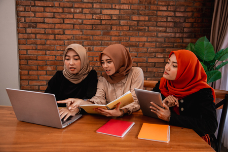 Group of college student, friends with laptop, digital tablet and books