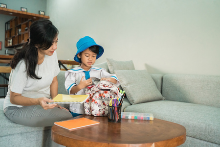 mom help her little girl preparing school stuff on her daughtess backpack