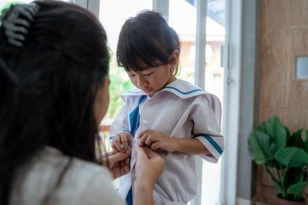 Kleinkind Kind bereitet sich morgens mit Mama auf die Schule vor