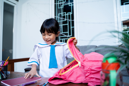 kid wearing school uniform put some book in to her backpack Stock fotó