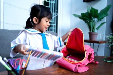 independent young kindergarten student preparing her own stuff before going to school