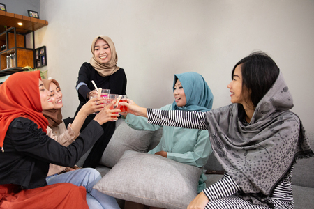 Veiled women drink cheers when breaking their fast