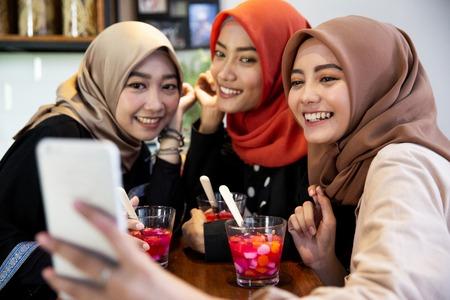 Veiled young women relaxing using smartphone for selfie Stok Fotoğraf