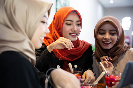 hijab women and friends using digital tablet while waiting breaking their fast Stok Fotoğraf