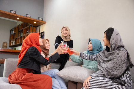 Veiled women chatting and drink cheers when breaking their fast
