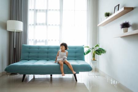 little girl sitting on a comfortable sofa