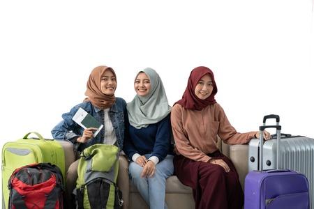 muslim woman traveler sitting with suitcase