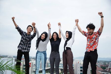 Young people hanging out and raise hand on the building rooftop