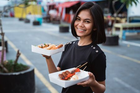 Asian young woman carrying a street food grilled