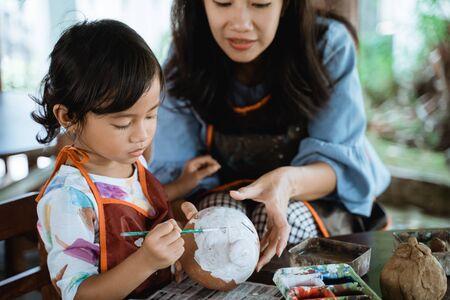Tochter lernt etwas über das Malen von Farbe
