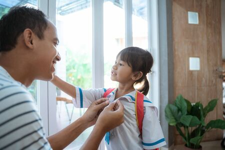 father help her toddler kid preparing for school in the morning Banco de Imagens