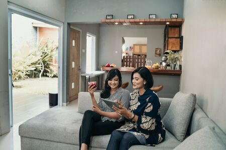 Daughter give a glass of cocktail to her mother at living room