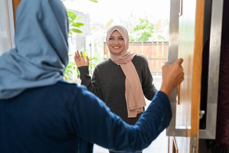 Mother opened the door for her daughter to go home Stock Photo