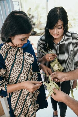 mother and daughter learning how to make a woven wrapper of ketupat