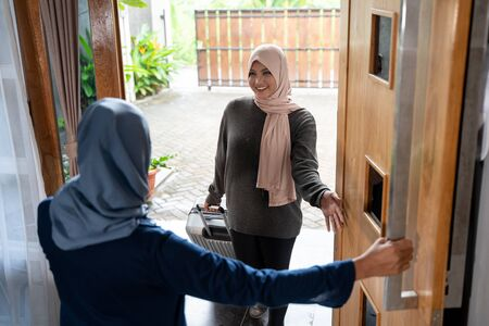 Mother opened the door for her daughter to go home during the Ramadan holiday