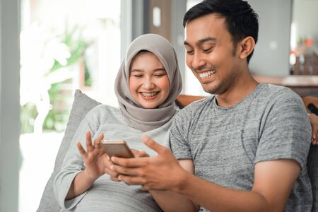 wife pregnant and husband using smartphone Standard-Bild