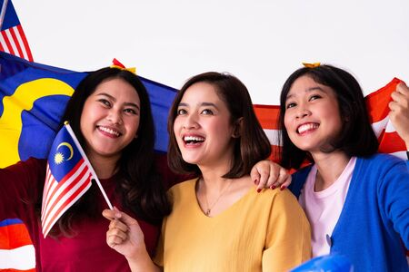 three malay woman holding malaysian national flag
