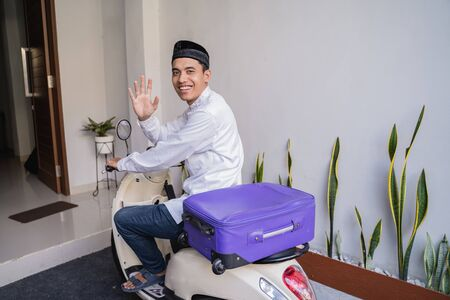 muslim man ride motorcycle for idul fitri    carrying suitcase Stock Photo