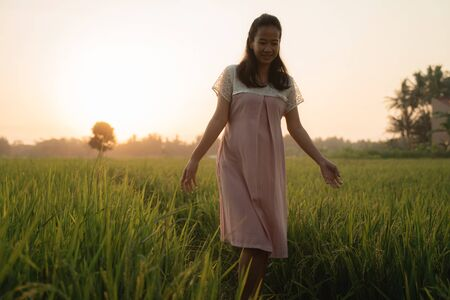 pregnant woman in rice field on sunset day