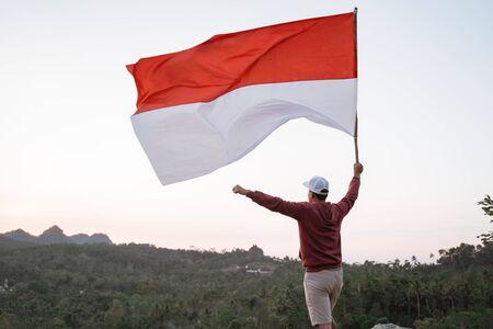 Hombre con bandera de Indonesia de Indonesia en la cima de la montaña