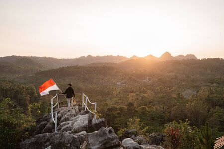 man with indonesian flag of indonesia on top of the mountain Stock Photo